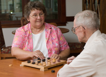 Older man and women playing a board game
